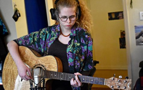 Gracie Caggiano '21 playing a guitar part for one of August Moon's tracks.