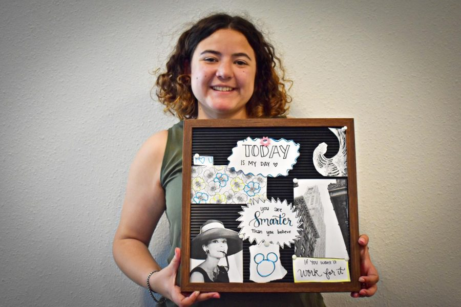 Naomi Johnson '22 poses with her vision board. Johnson and others use vision boards to help focus on what they want in life. Johnson suggests to identify one's goals and finding words and images to visualize that.